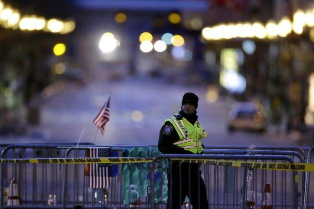 Policial caminha ao longo de barricada em Boylston Street, perto da linha de chegada da Maratona de Boston onde ocorreram as explosões do atentado   Matt Rourke/Associated Press