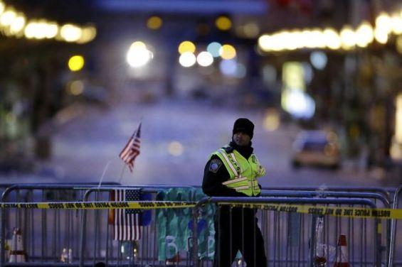 Policial caminha ao longo de barricada em Boylston Street, perto da linha de chegada da Maratona de Boston onde ocorreram as explosões do atentado | Matt Rourke/Associated Press