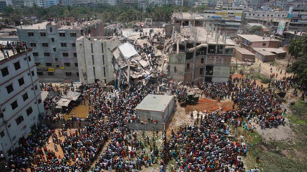 Multidão se aglomera ao redor do predio que desabou em Bangladesh enquanto bombeiros e voluntários tentam resgatar sobreviventes presos nos destroços   Andrew Biraj/Reuters